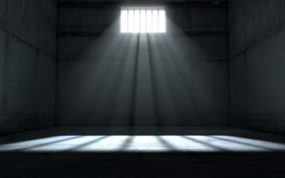 A jail cell interior with a barred up window and light rays penetrating through it casting an image of the words freedom - 3D render